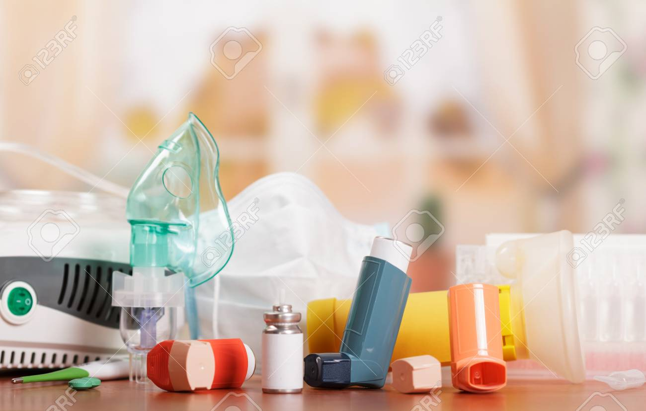Compressor and ultrasonic nebulizers, aerochamber, inhaler, thermometer and medicines to treat asthma on abstract pink background. - 88001708