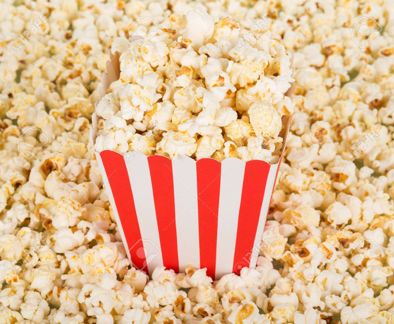 A large square box of popcorn and a lot of popcorn around. Background. Close-up. - 88002218