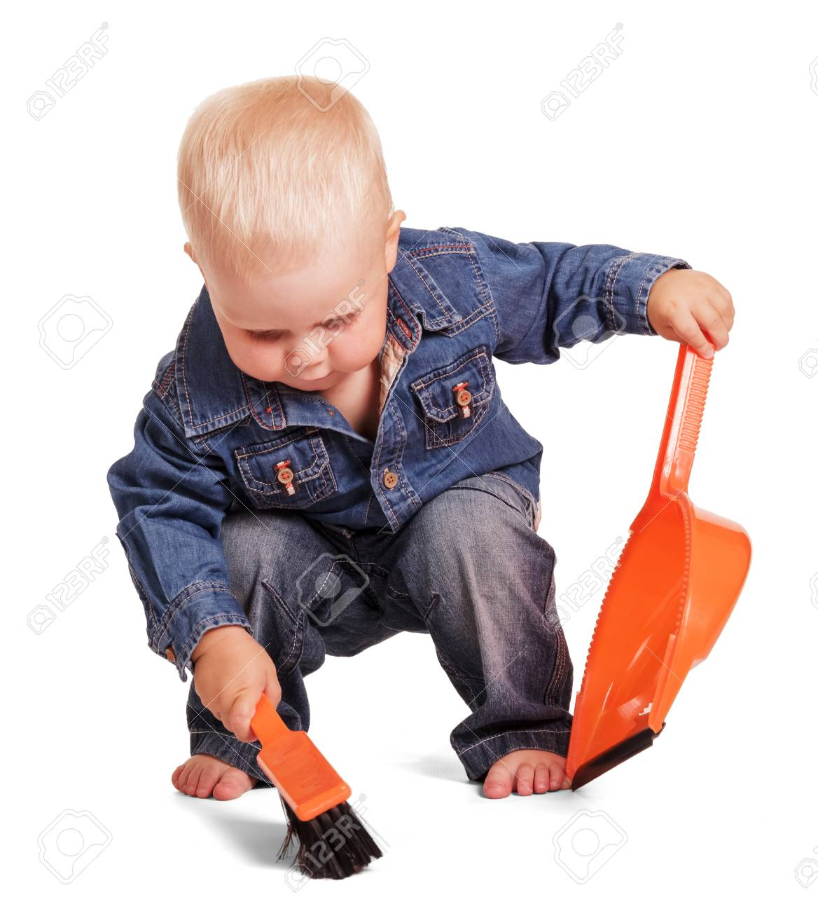 eea9dc1d8d0 Cute little boy in a blue shirt and jeans, holding a dustpan and brush  sweeps