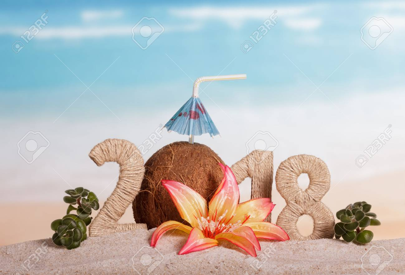 New Year inscription 2018, coconut with drinking straw and umbrella instead of the number 0, flower and green leaves on the sand. - 88003413