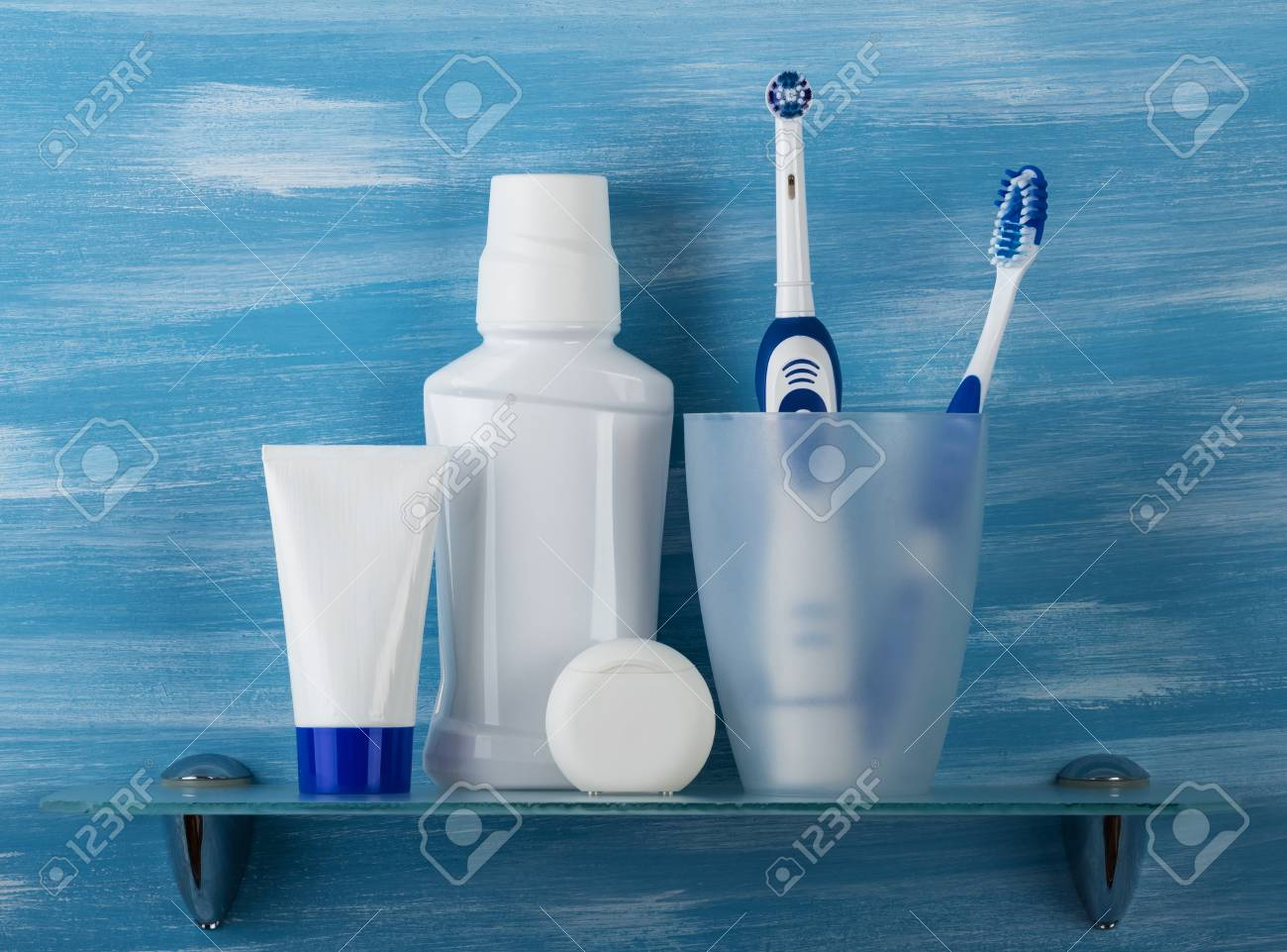 Set For Oral Care And Two Toothbrushes In A Glass, On Small Shelf ...