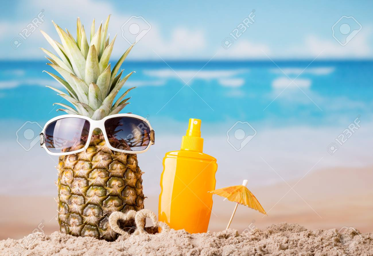 Pineapple with sunglasses, umbrella and sunscreen, on beach - 101334292