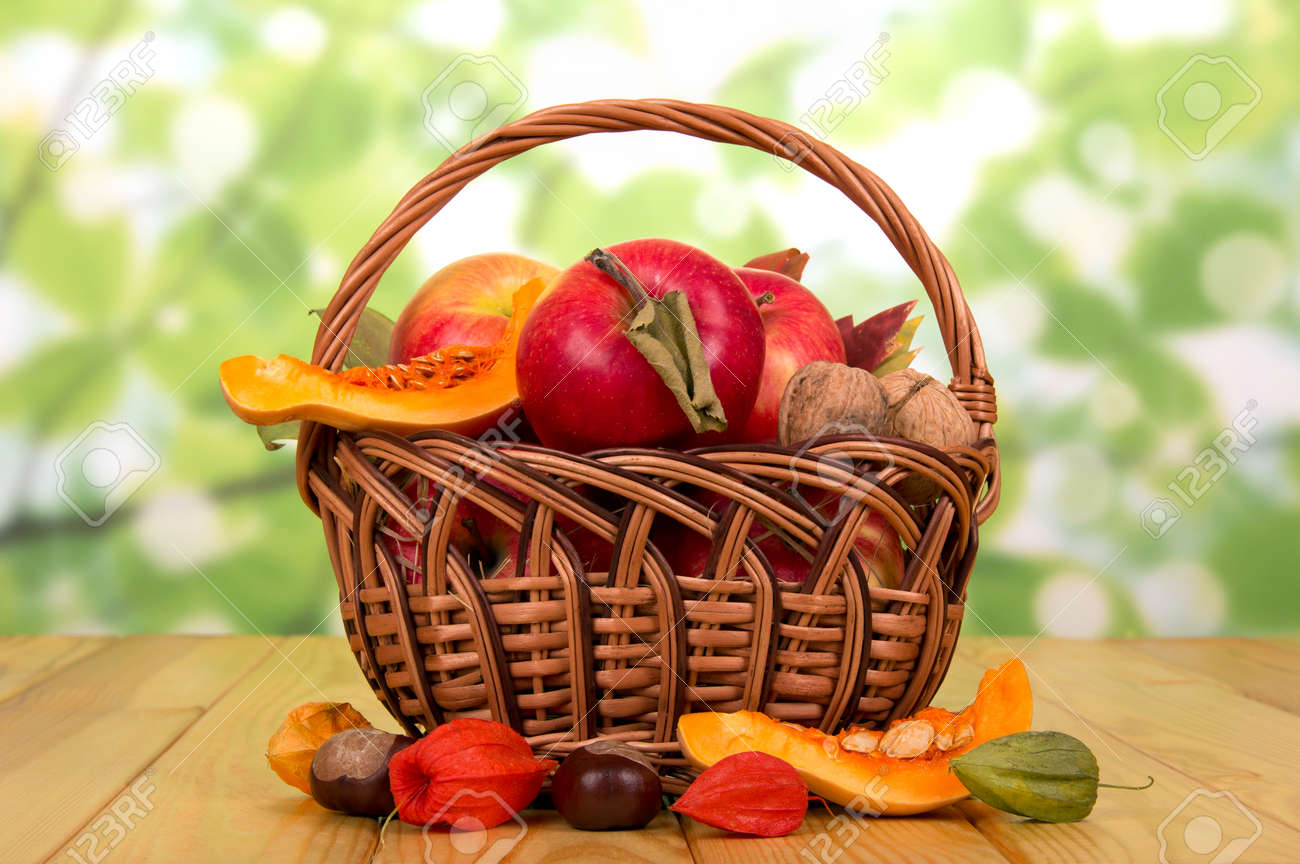 Basket with ripe apples, walnuts, slices of pumpkin and chestnuts near on an abstract green background. - 143192748
