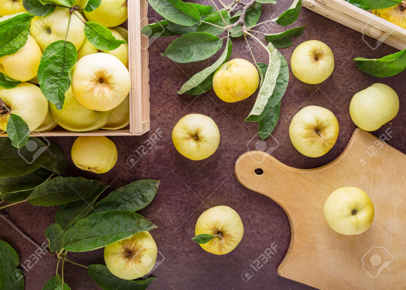 Top view. Fruit harvest. Fresh juicy apples with leaves in a wooden box on a dark background - 167288810