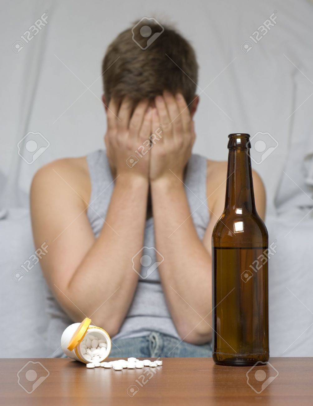 Beer bottle and drugs on the table. Depressed and lonely man. Stock Photo - 15628946