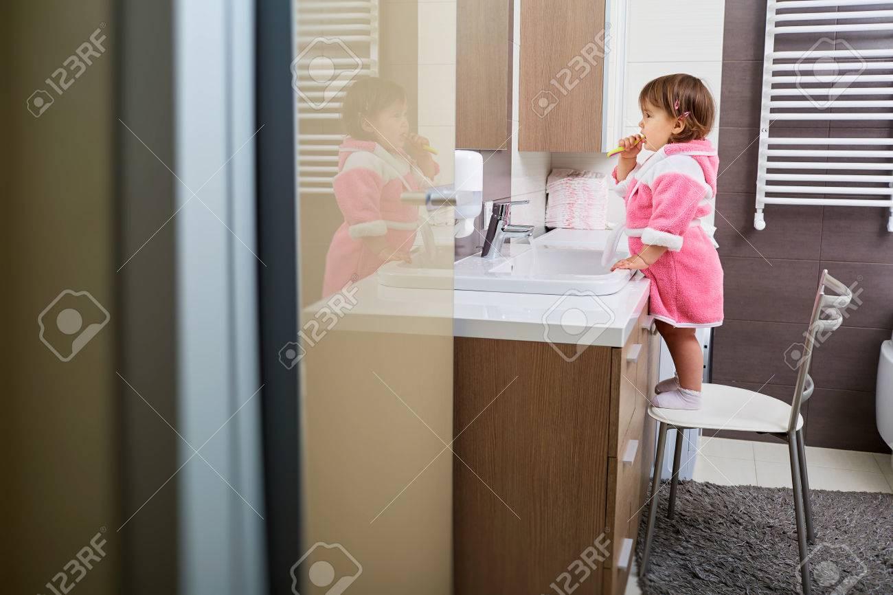 Little girl brushing her teeth in the bathroom. - 55754342