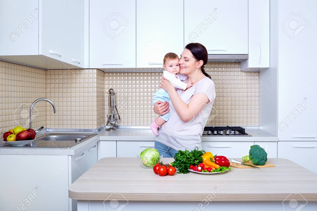 Mother and Baby kissing and hugging at Home. Mom and Her Child in the kitchen .Healthy eating. Diet,dieting concept. - 57867546