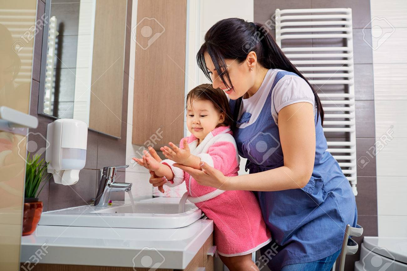Mother and daughter washing their hands in the bathroom. Care and concern for children. - 61411030