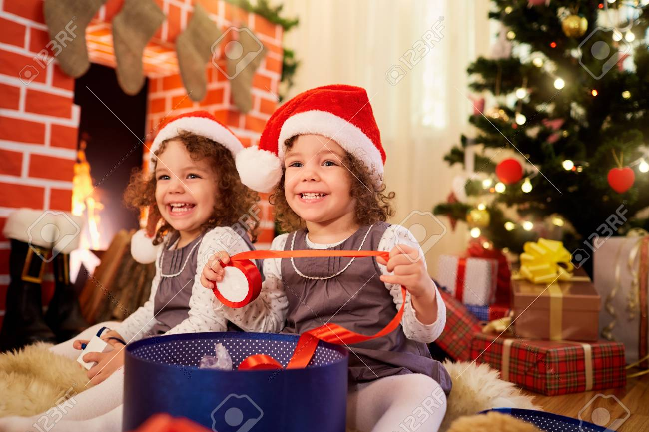 b724222bf Little girls twins at Christmas sitting on the floor in Santa..