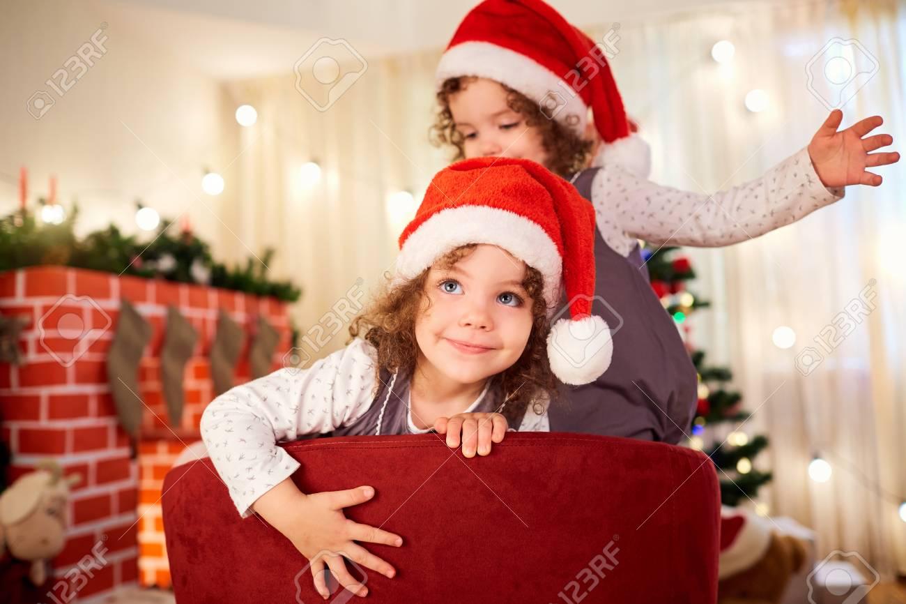 Kinderbild Am Weihnachten. Gelocktes Nettes Mädchen In Sankt-Hut Zur ...