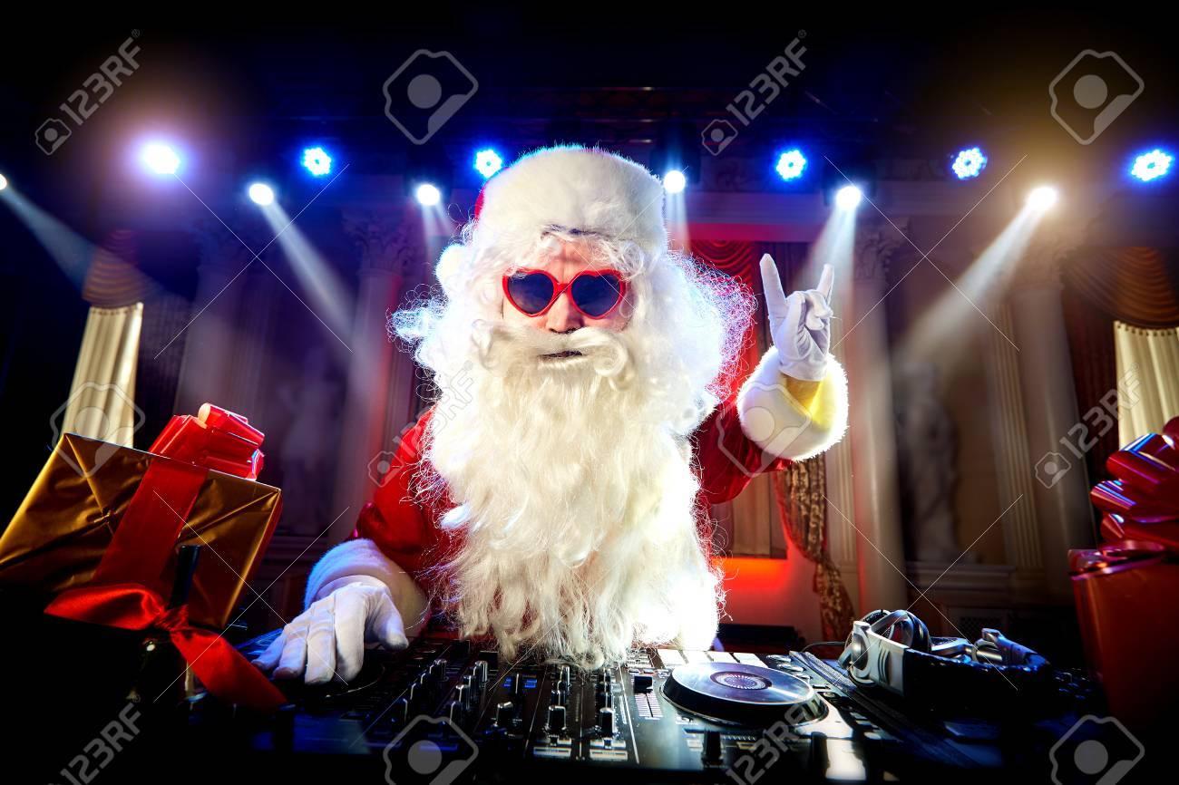Dj Santa Claus mixing at the party at Christmas, raised his hand up - 66938852