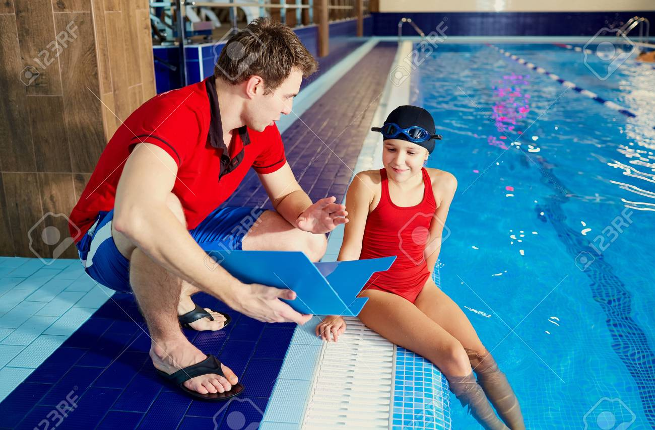 Coach,tranier to swimmer girl at the pool discussing with athlete. - 69574713