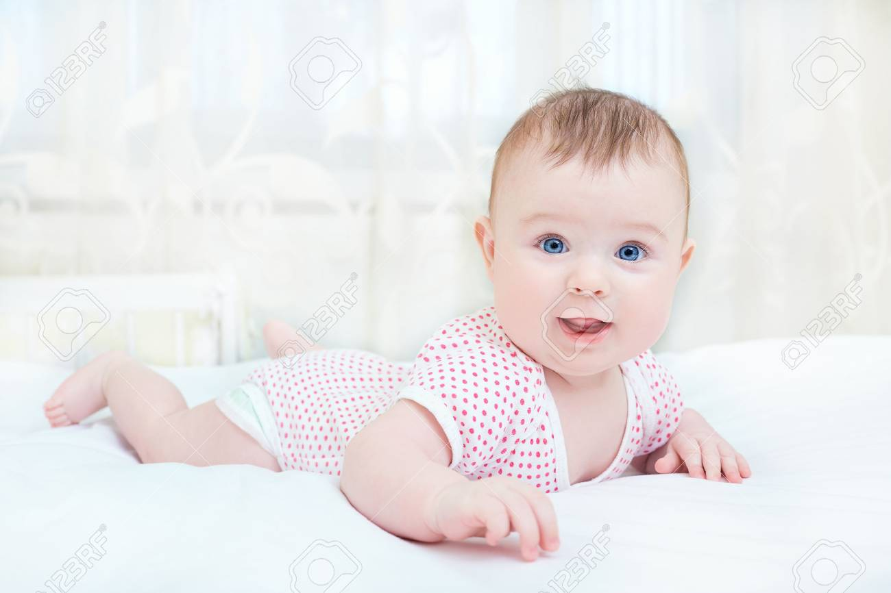 Cute baby smiling while lying on a white bed. - 72087009