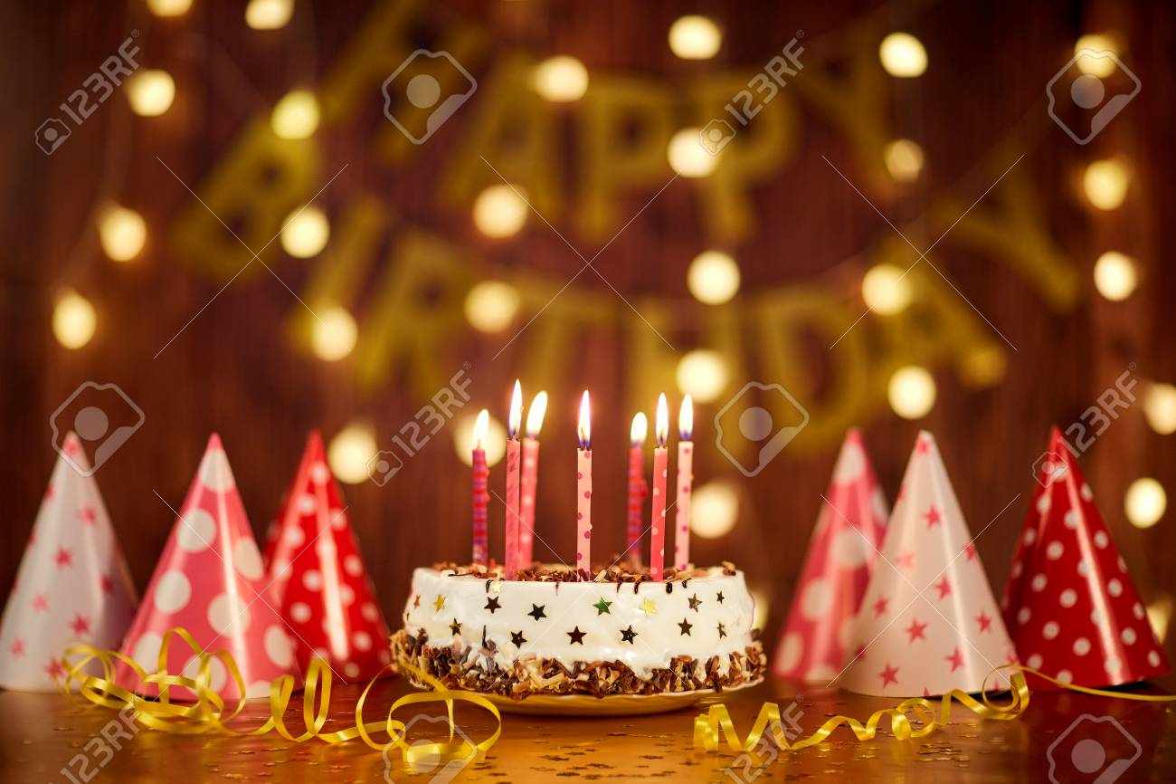 Happy Birthday Cake With Candles On The Background Of Garlands And Letters Stock Photo