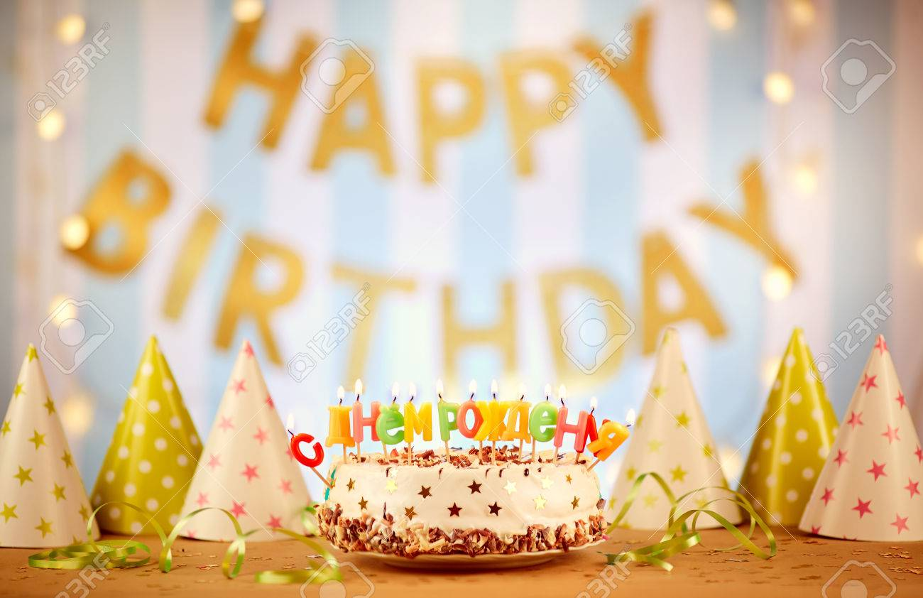 Happy Birthday Cake With Candles Russian Letters On The Background Of Garlands Stock Photo