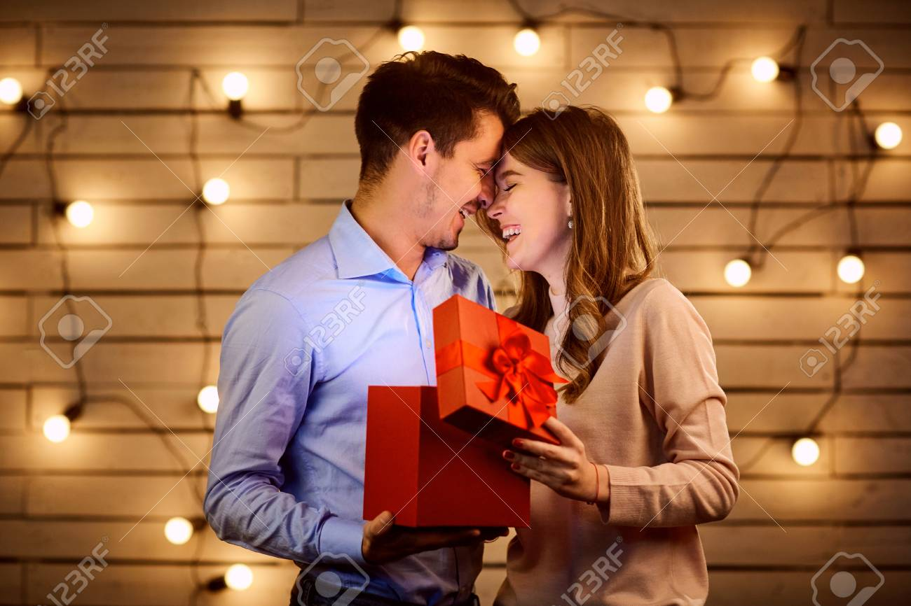The Guy Gives A Gift Box To His Girlfriend Young Couple On Holiday