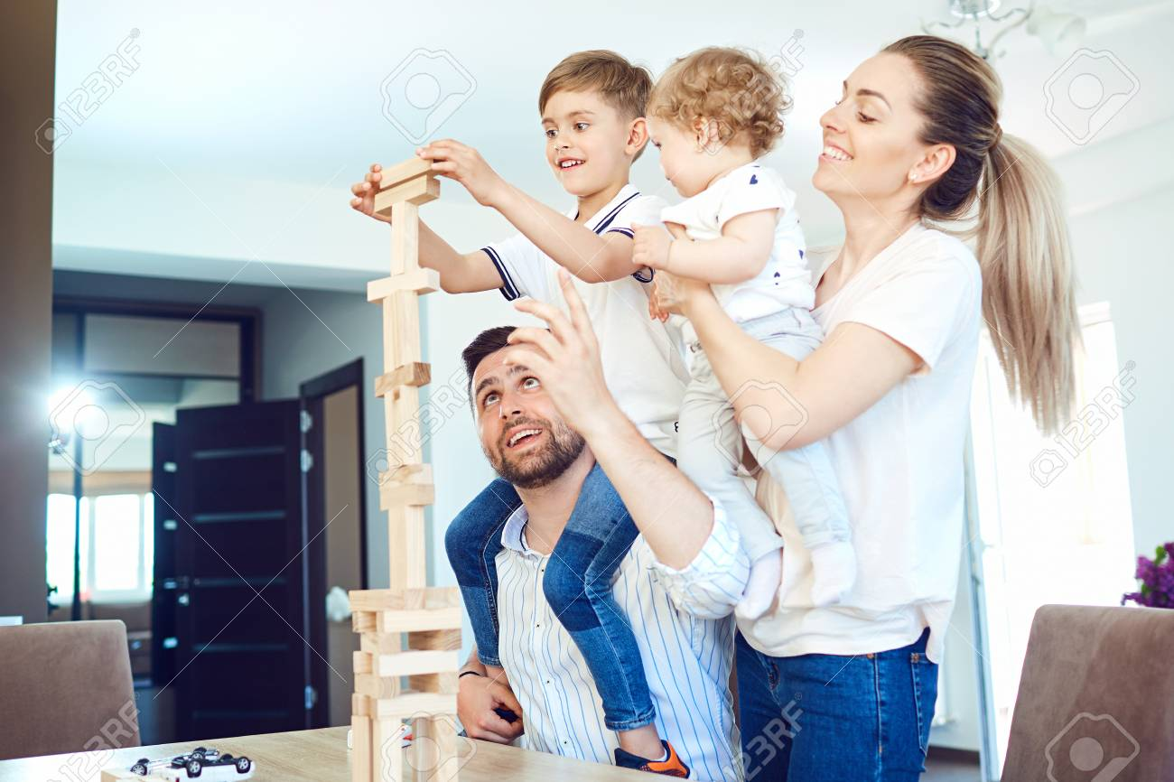 A cheerful family plays board games sitting at a table indoors. - 101656802