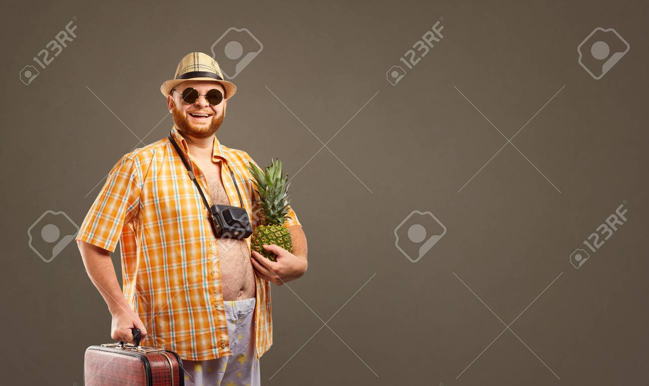 A funny fat bearded tourist with a pineapple and a suitcase smiles against the background for the text. - 104006271