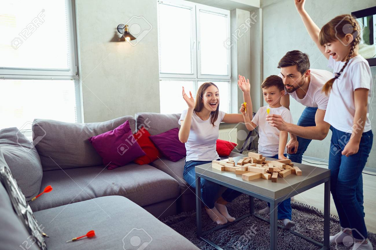 Happy family playing board games at home. Mother, father and children play together. - 107723023