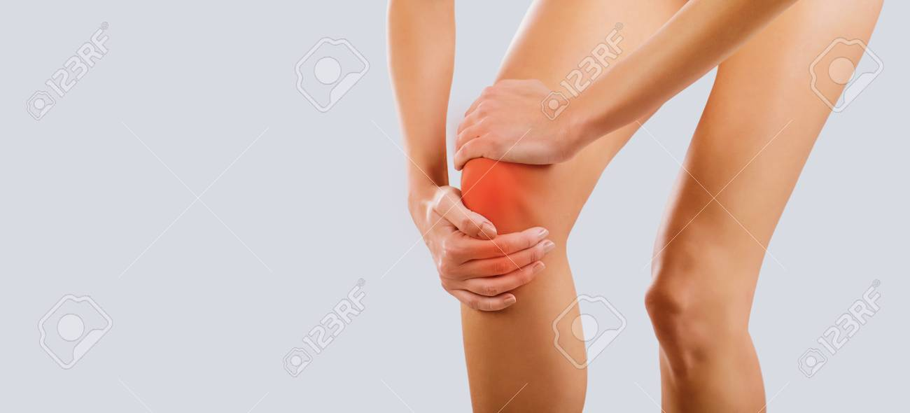 Pain, injury to the knee. A woman holds her knee with her hand. - 118833442