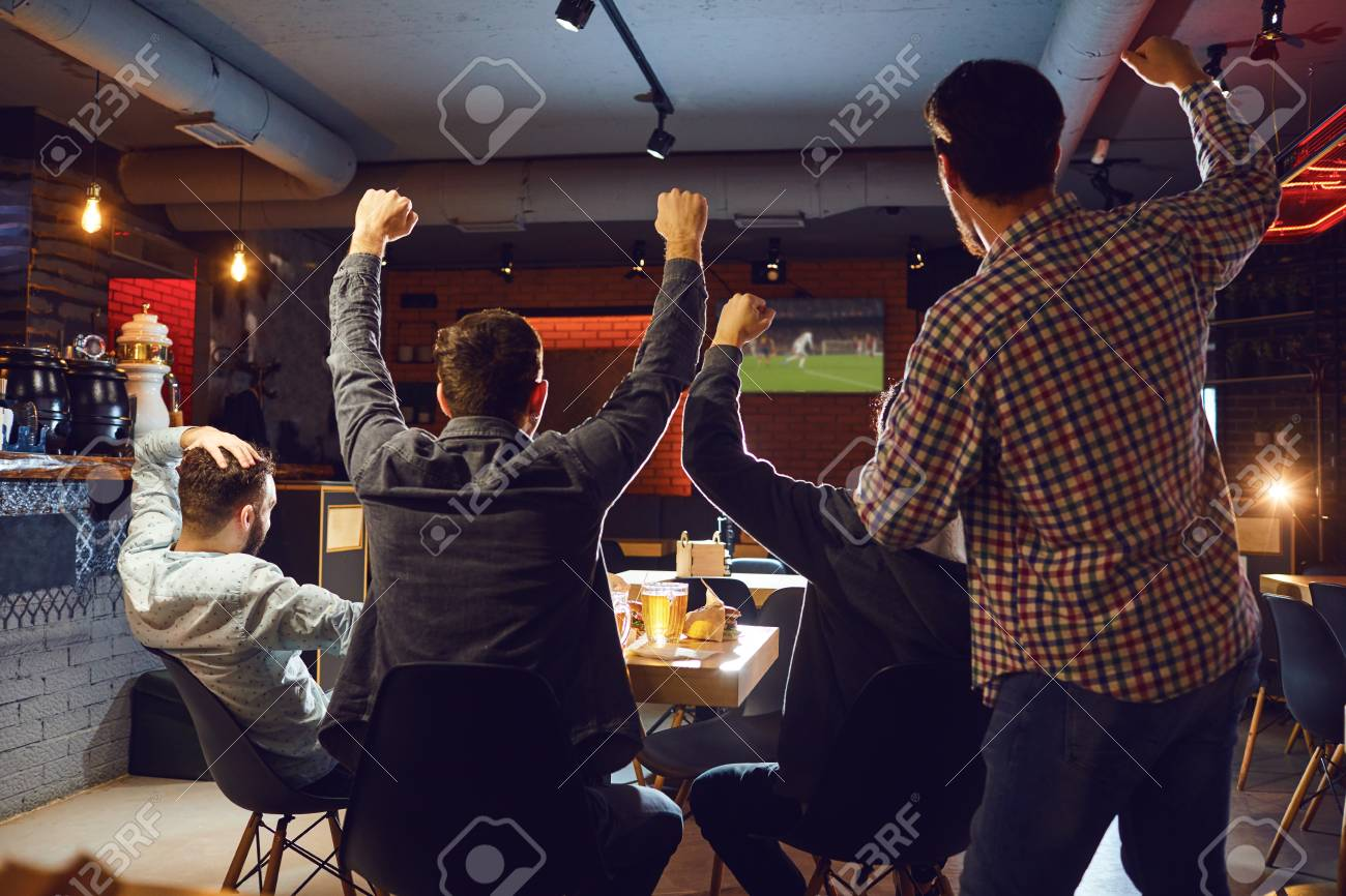 Friends watch sport tv in the pub. Young people support their team in the bar. - 119645540