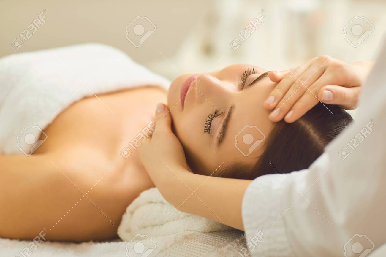 Spa treatment at beauty salon. A young woman gets a facial massage at the cosmetology center. - 122063919