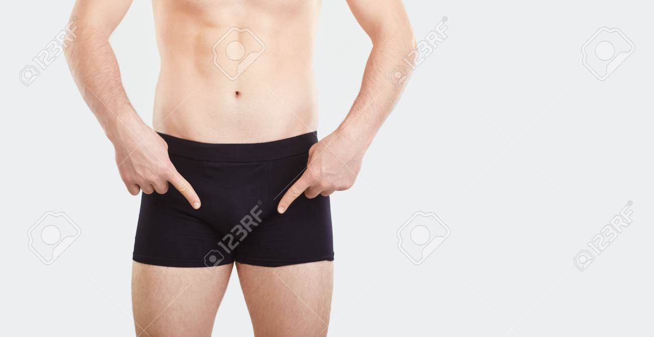 A man in black underwear points his finger at the penis. The concept of intimate problems. - 122065229