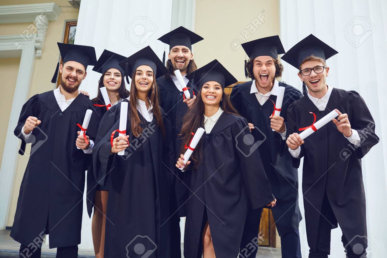 A group of graduates with scrolls in their hands are smiling against the background of the university. Graduation.University gesture and people concept. - 123332429
