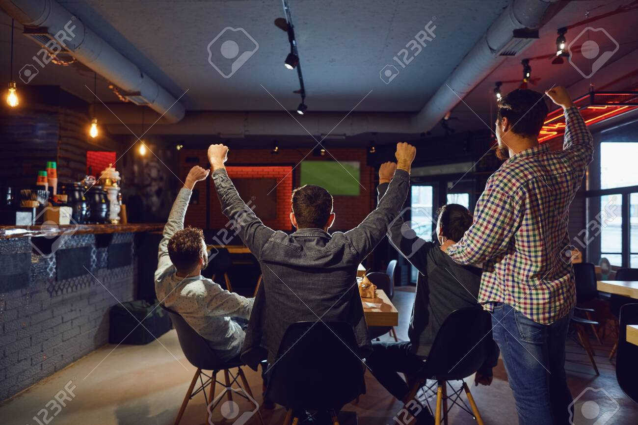 Friends in the sports bar support their team watching TV. - 129776724