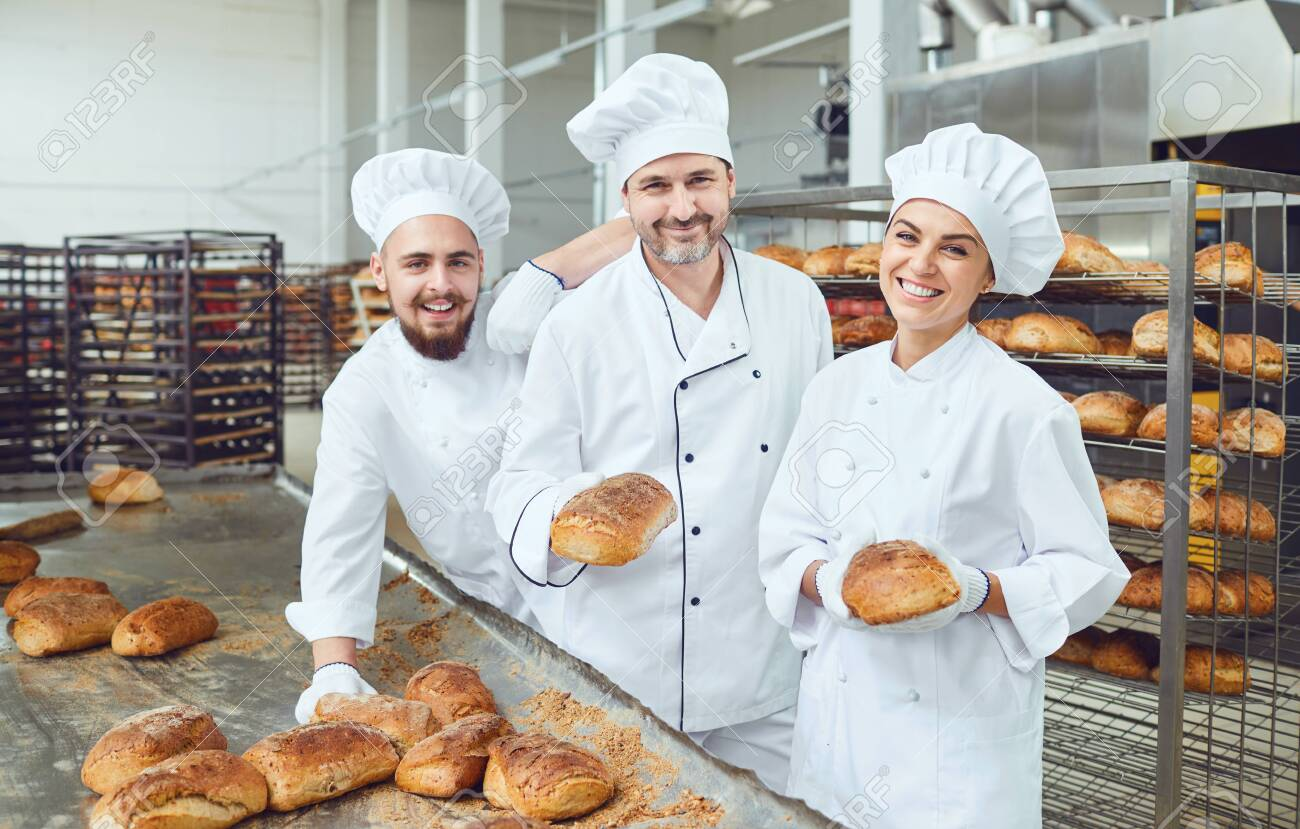 Beautiful bakers smiling holding fresh bread in their hands in a bakery factory - 131890000