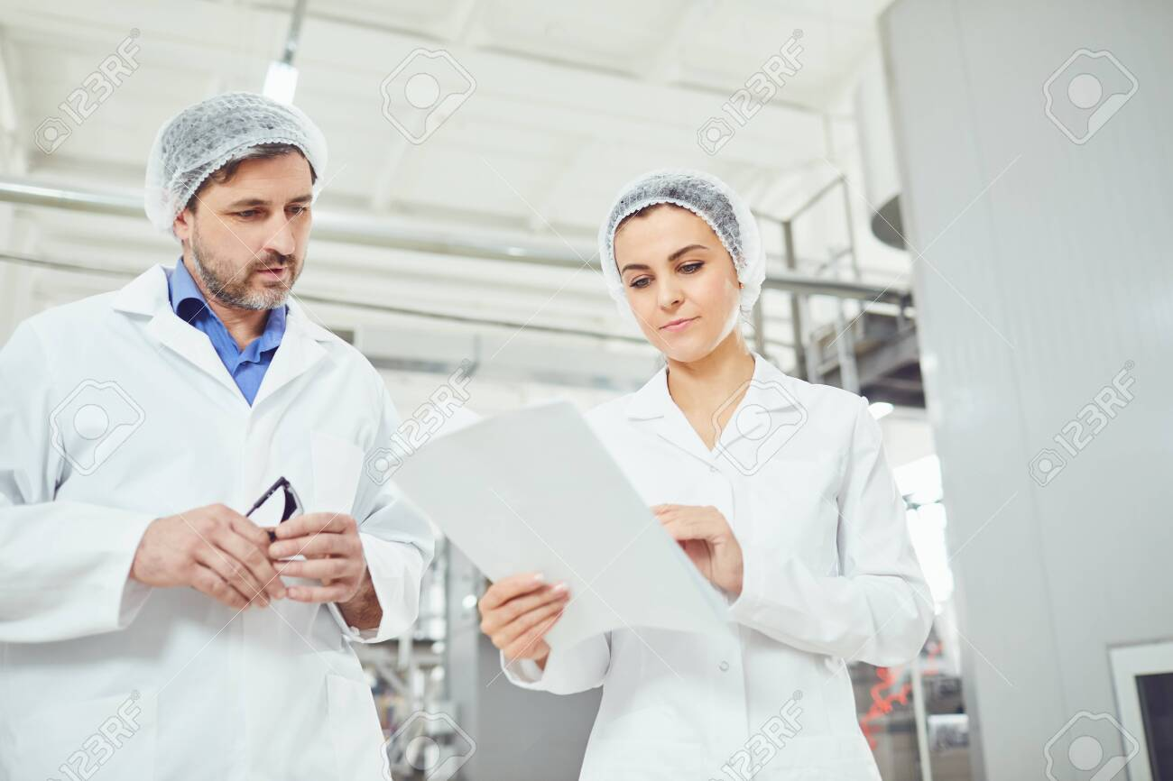 Two technologists in lab coats and masks control the production process at the factory. - 129996810