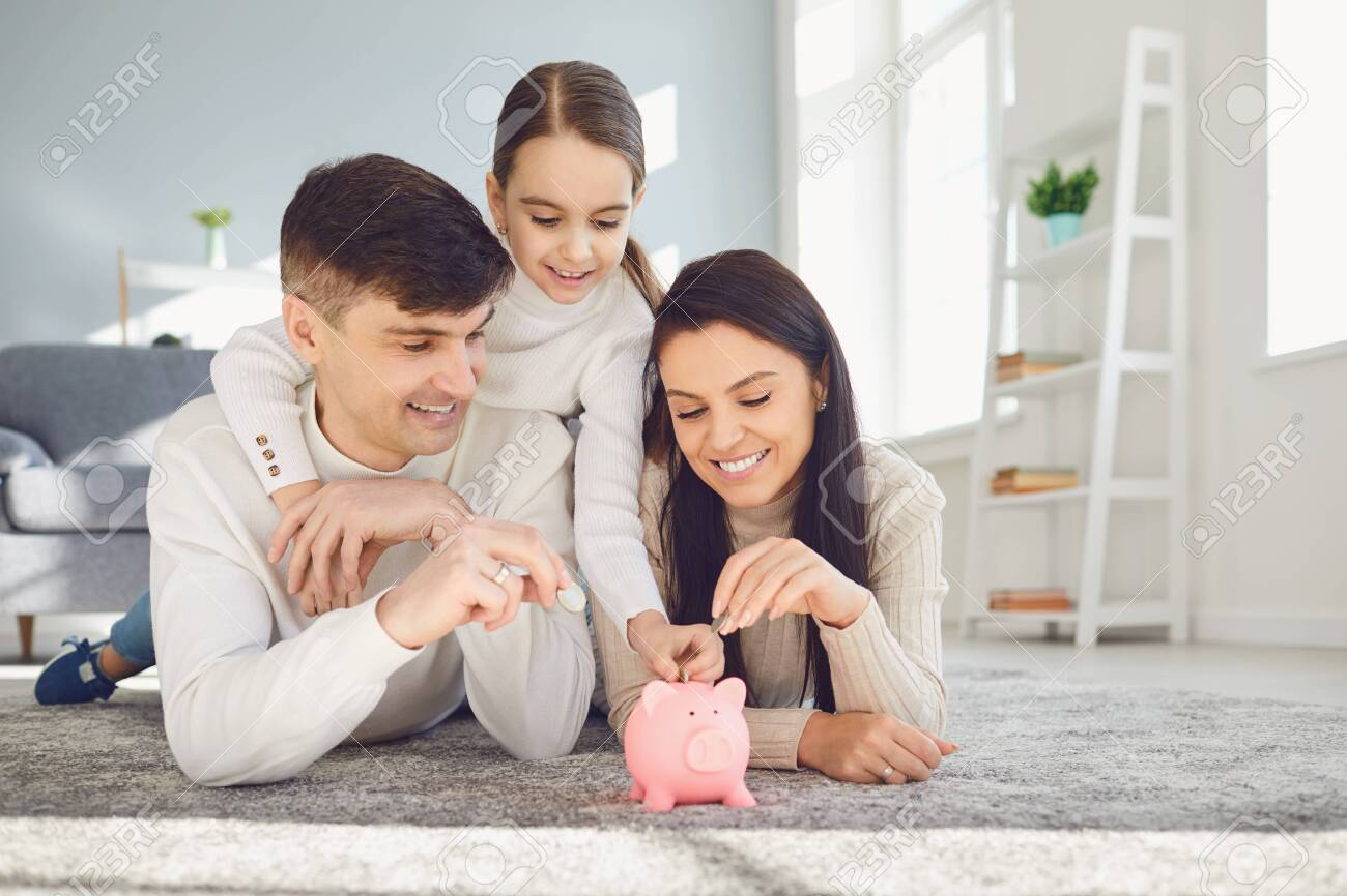 Happy family saves money in a piggy bank pig. Money finance saving concept. - 140231139