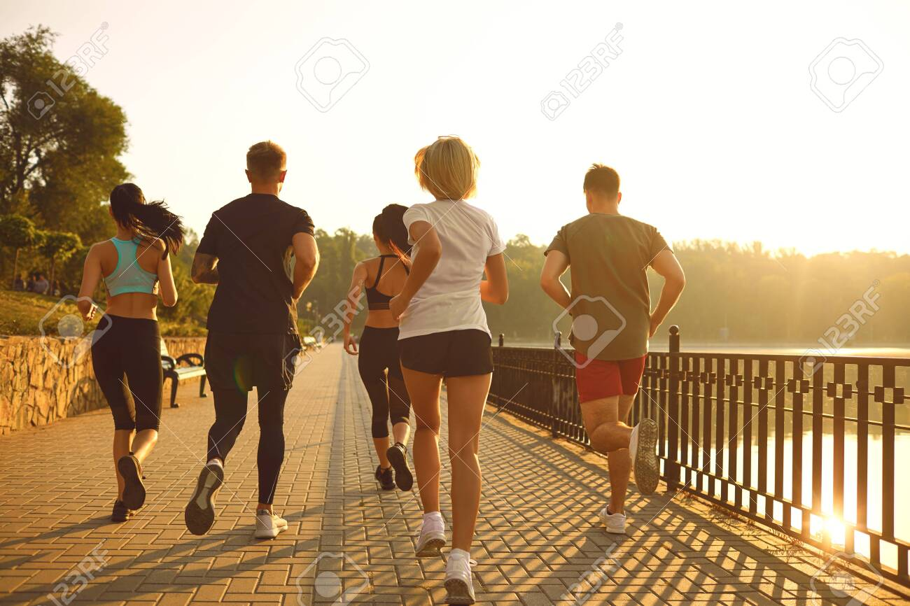 A group of young people in sportswear are running in the park. Back view. - 140191526