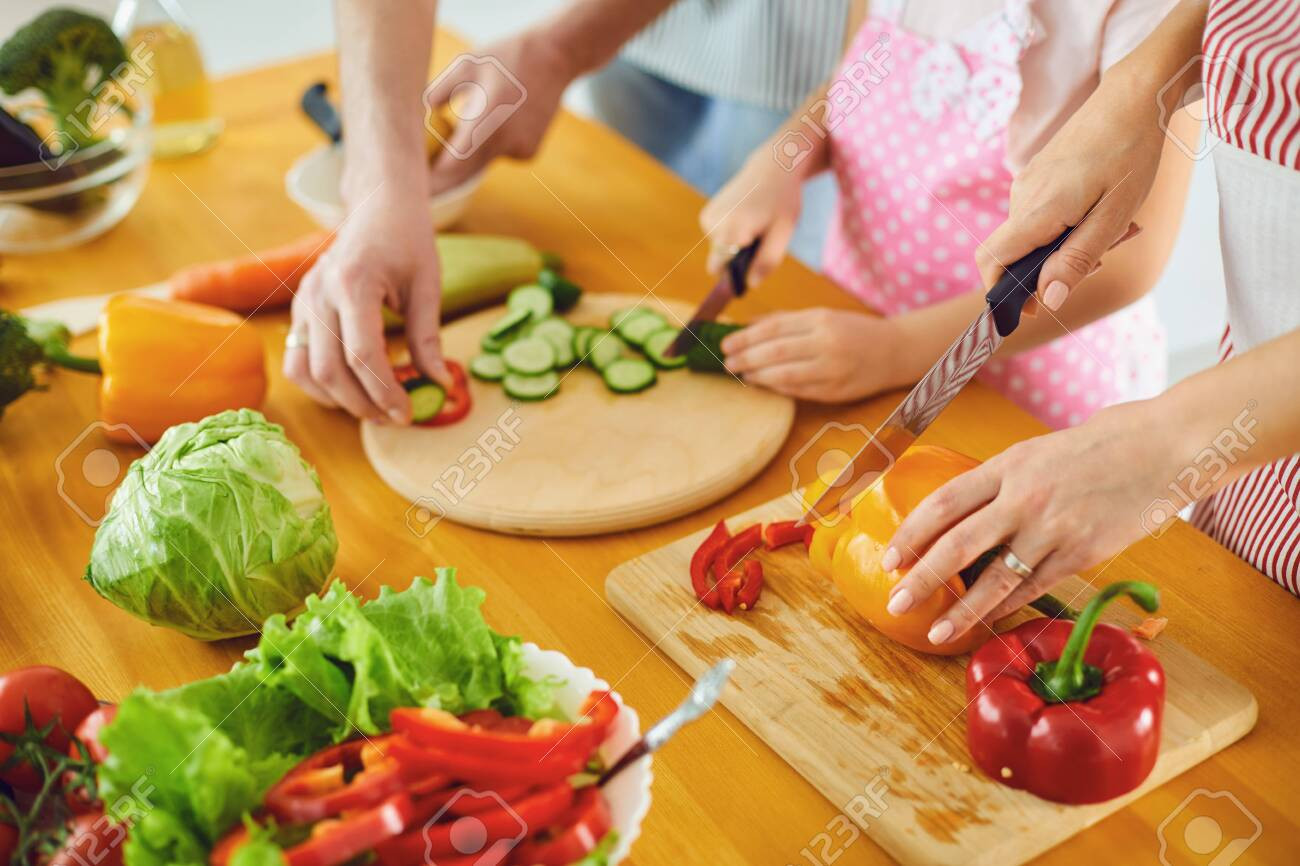 Faceless. Family hands prepare fresh vegetables salad on the table in the kitchen. Mother's hands cut vegetables with a knife. Healthy eating - 143045070