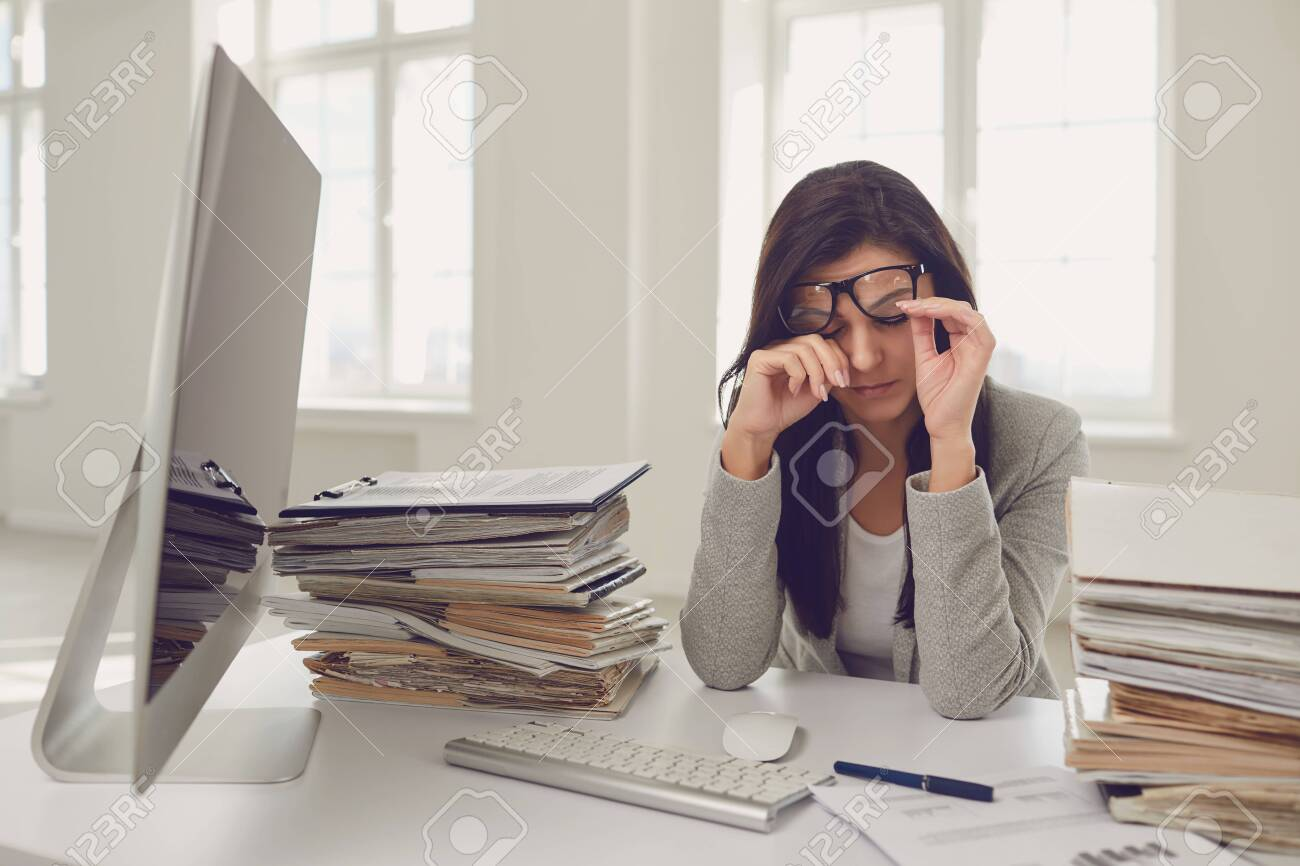 A lot of work in the office. Tired busy businesswoman is working with computer. Female worker covers his face with his hands while sitting at the workplace. - 146229297