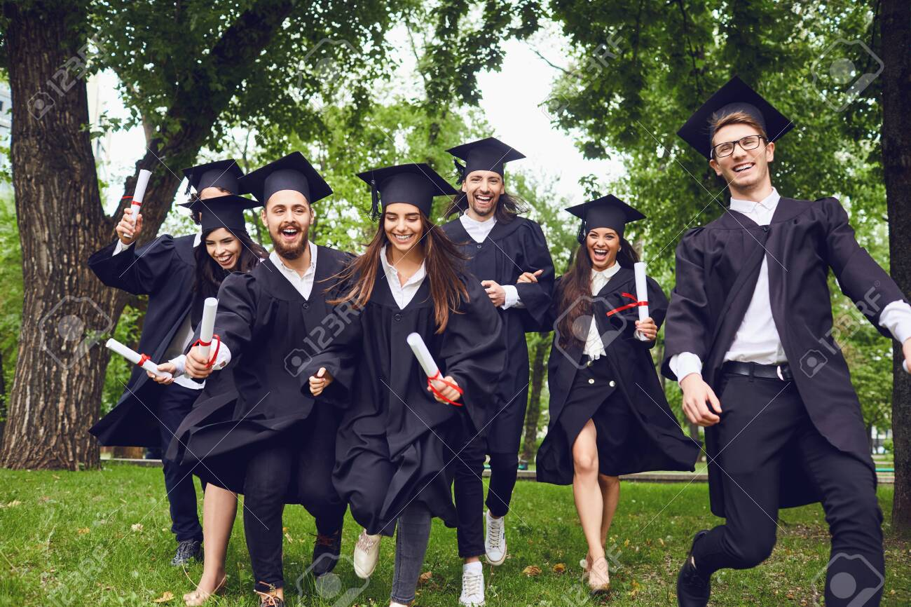 A group of graduates with scrolls in their hands are smiling against the background of the university. Graduation.University gesture and people concept. - 150113491