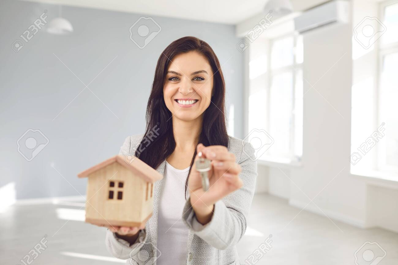 Woman seller broker realtor agent is a realtor with keys in hand against the background of a white real estate room apartment home. Sale purchase rent real estate mortgage. - 150551246