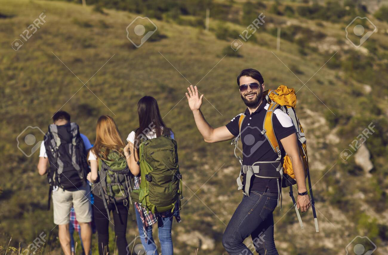 A group of hikers with backpacks are walking along the hill in the mountains in nature. Travel adventure people tourists. - 151965881