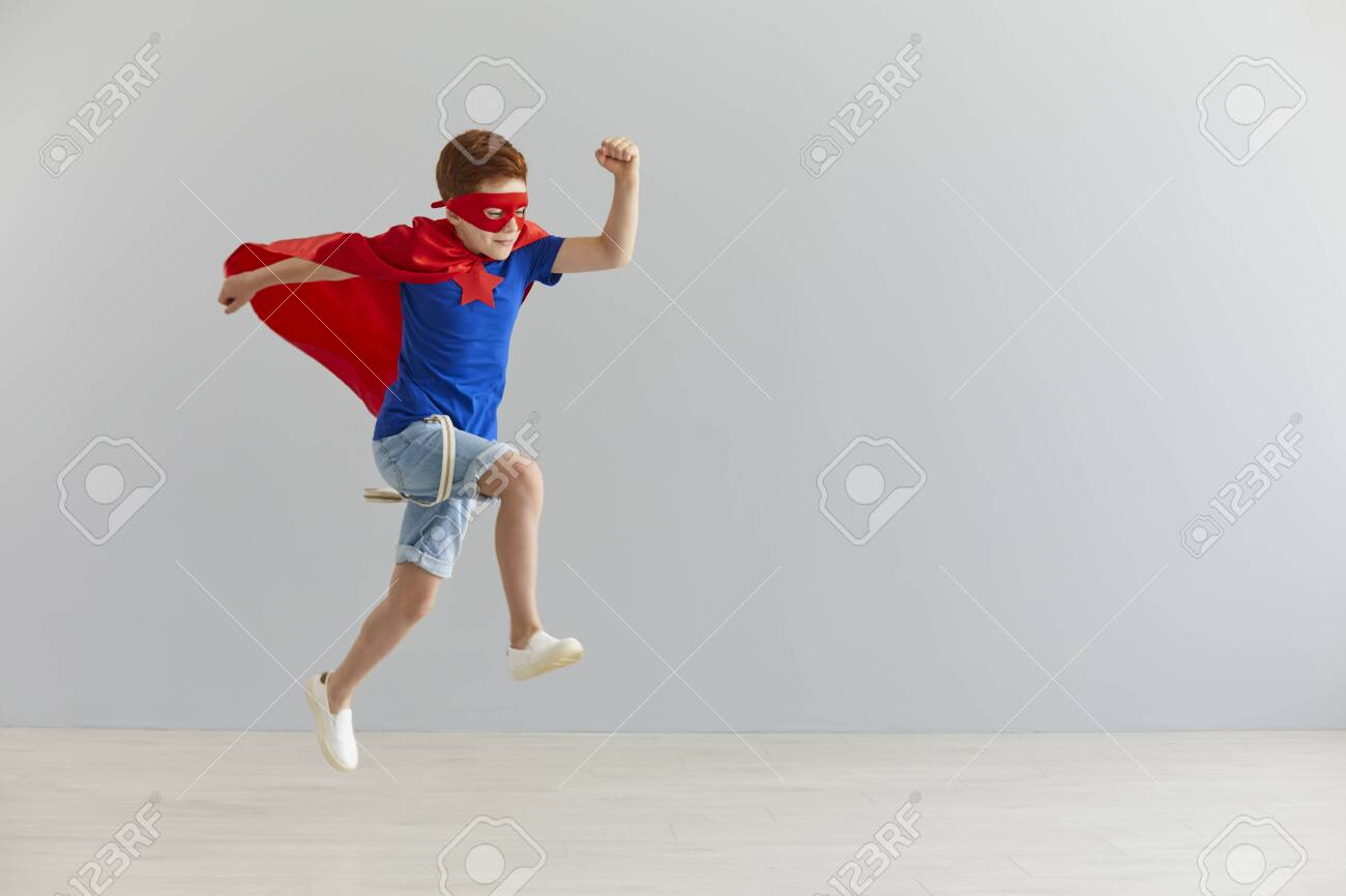 Happiness, freedom, childhood, movement and people concept, boy in red superhero cape and mask jump and fly. - 155033827