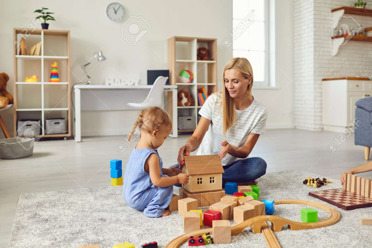 Mom and child at home. Young mother playing with little son teaching him to build toy house. Happy nanny engaging toddler boy in fun activities with wood blocks on warm floor in cozy studio apartment - 155752279