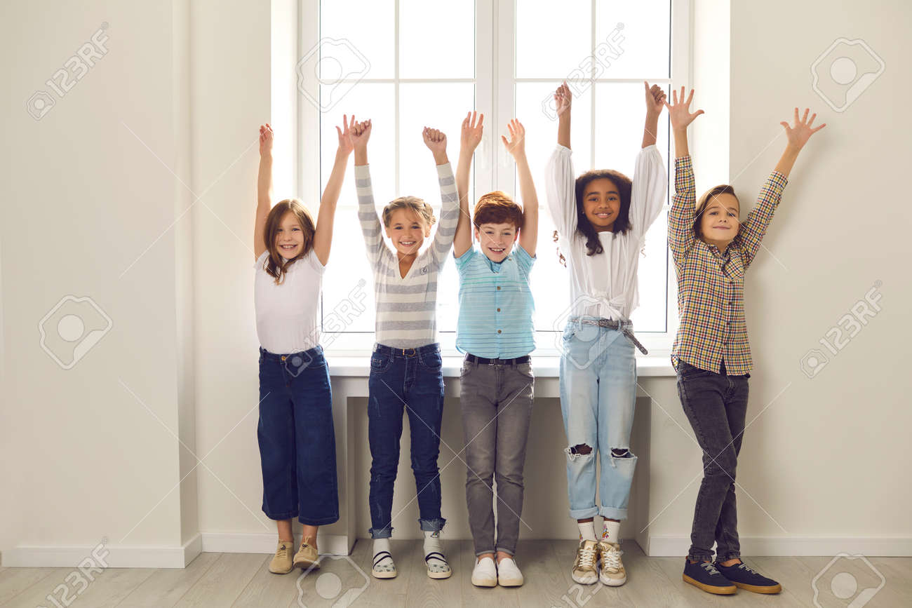 Group of diverse children of classmates stand with raised hands in the school corridor near the window during a break. Boys and girls are happy with a successfully written test. Positive emotions. - 158151668
