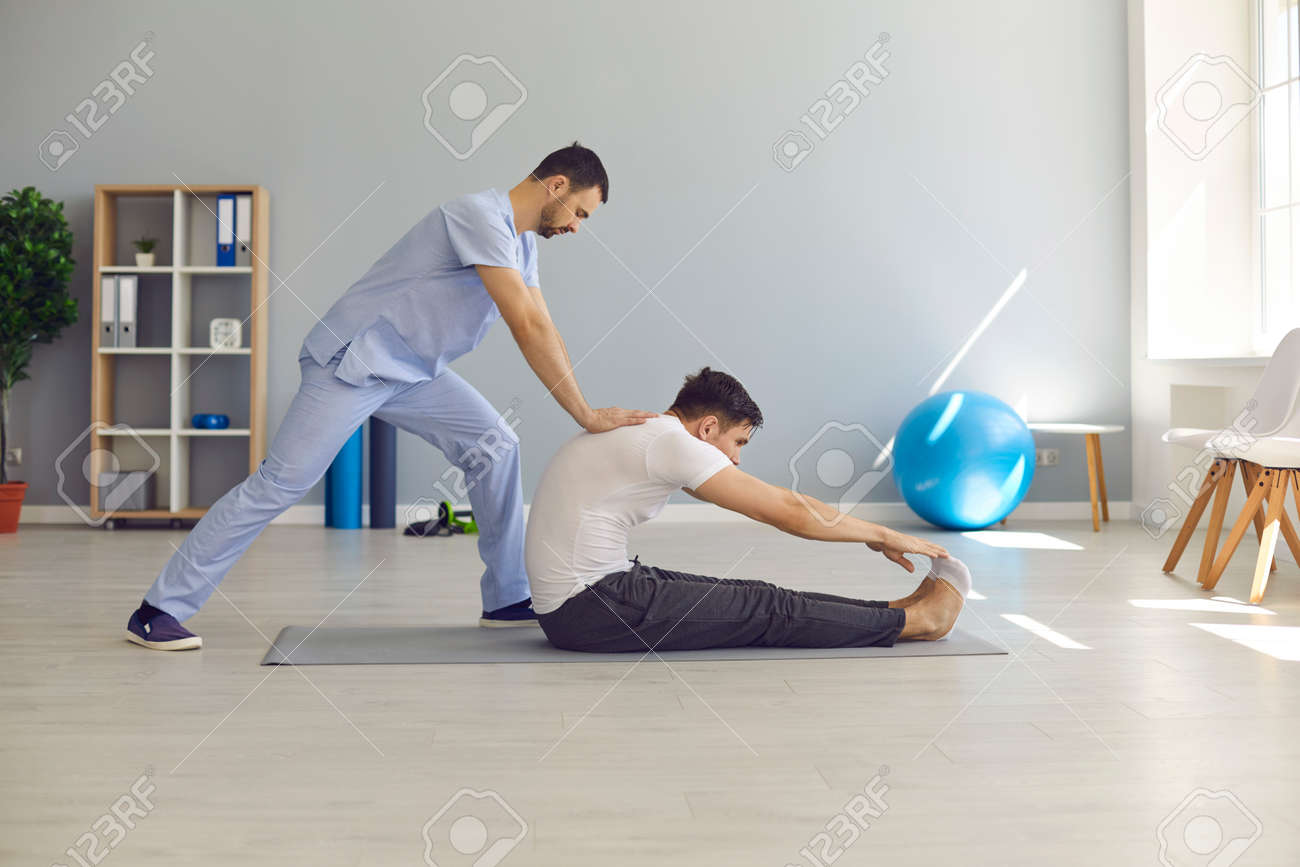 Professional man chiropractor or osteopath stretching man patients back and making rehabilitation theapy for patient during visit in manual therapy clinic. Chiropractor during work concept - 158630595