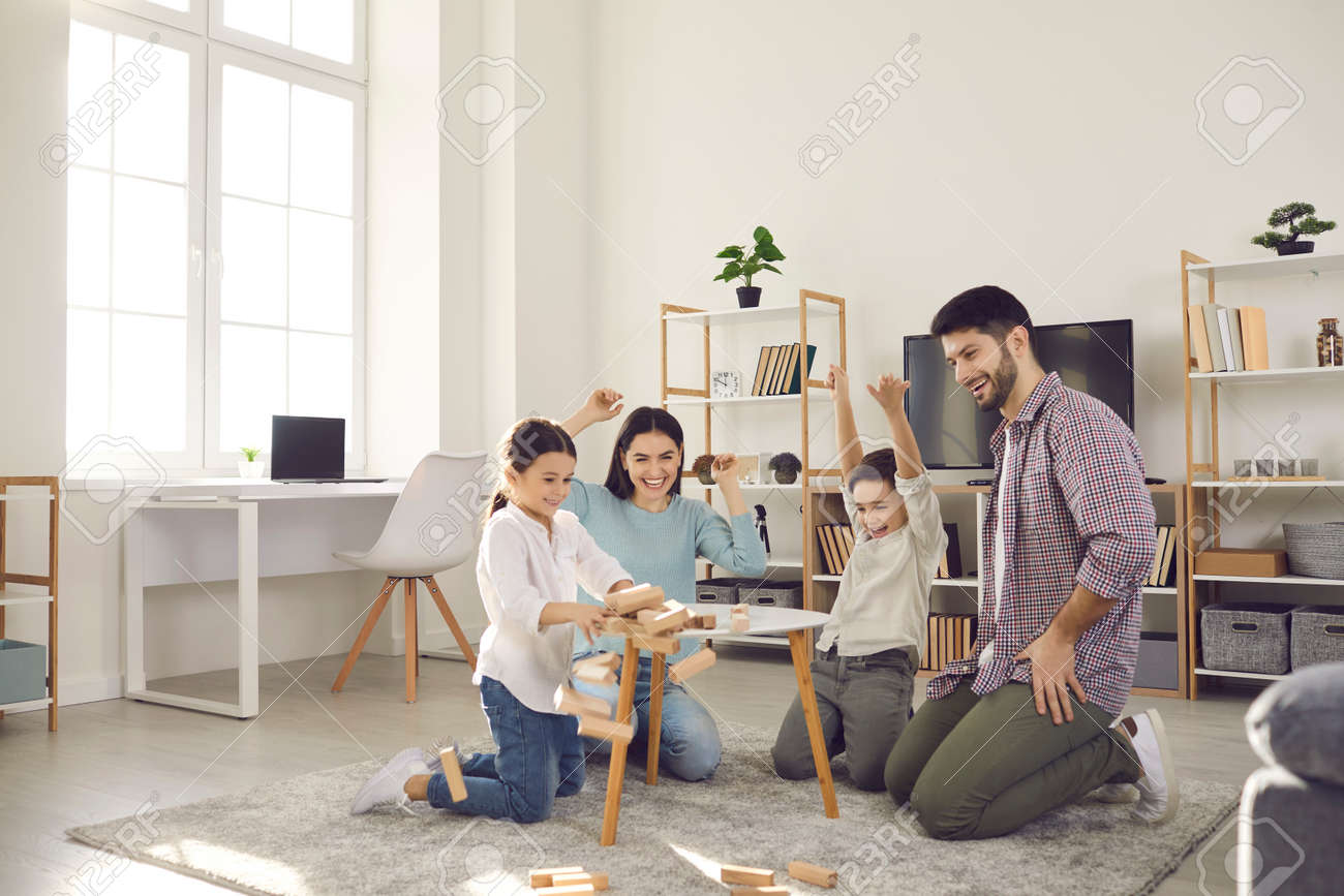Family weekend entertainment. Mom, dad, daughter and son play game sitting at a table from which a wooden tower falls. Fun board games for family leisure. Stay at home activity for kids. - 164702819
