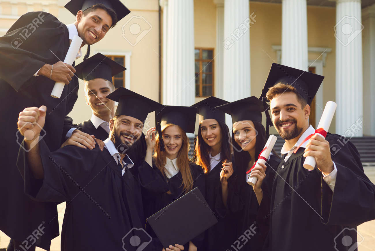 Group portrait of happy graduates near their alma mater. Smiling university students in traditional academic gowns and caps holding diplomas looking at camera after graduation ceremony - 167113532