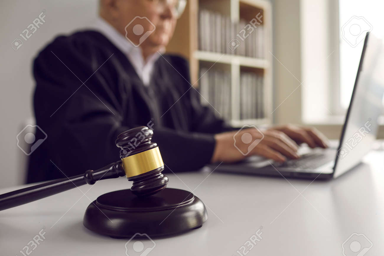 Close up of dark brown gavel on table on background of senior male judge working on laptop. Concept of law, justice, fairness and online legal advice. Blurred background. - 168771006