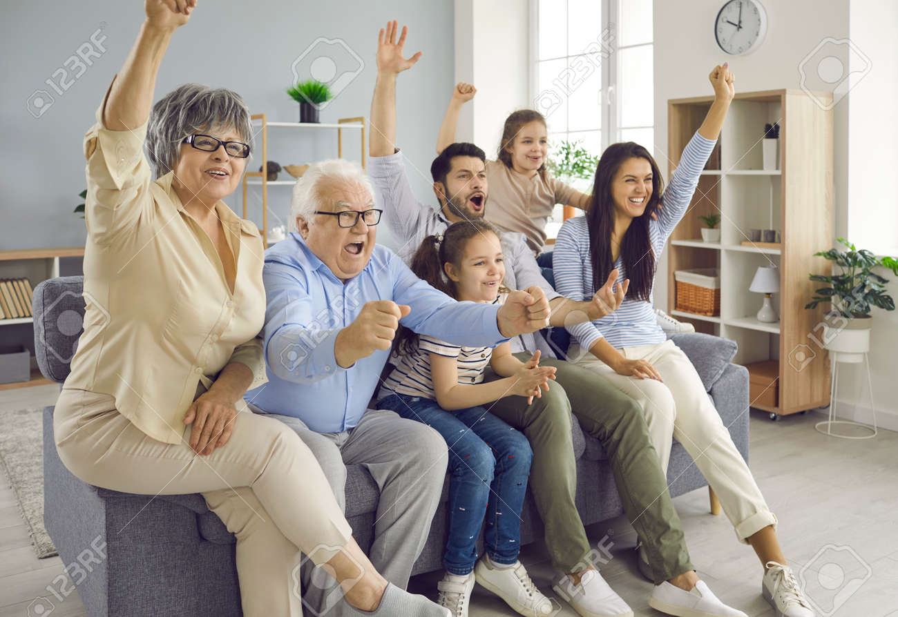 Fun from grandparents to children. Excited happy big family of different generations watching football match on sofa at home. Older and younger fans emotionally encourage their favorite team. - 173418609