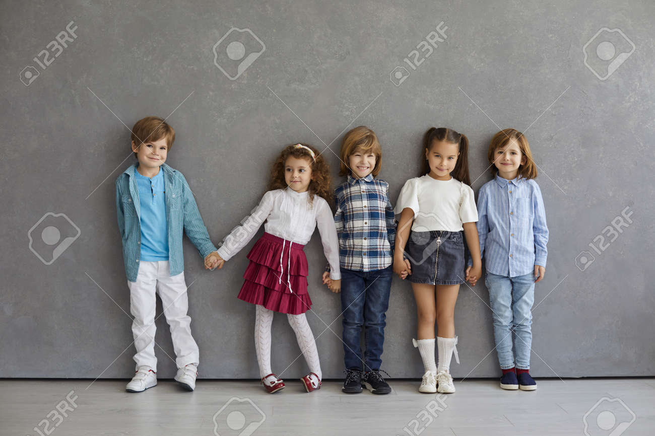 Portrait of cute and happy little boys and girls in casual clothes standing against the gray wall. Beautiful smiling and funny kids standing in a row holding hands. Childhood concept. - 173558157