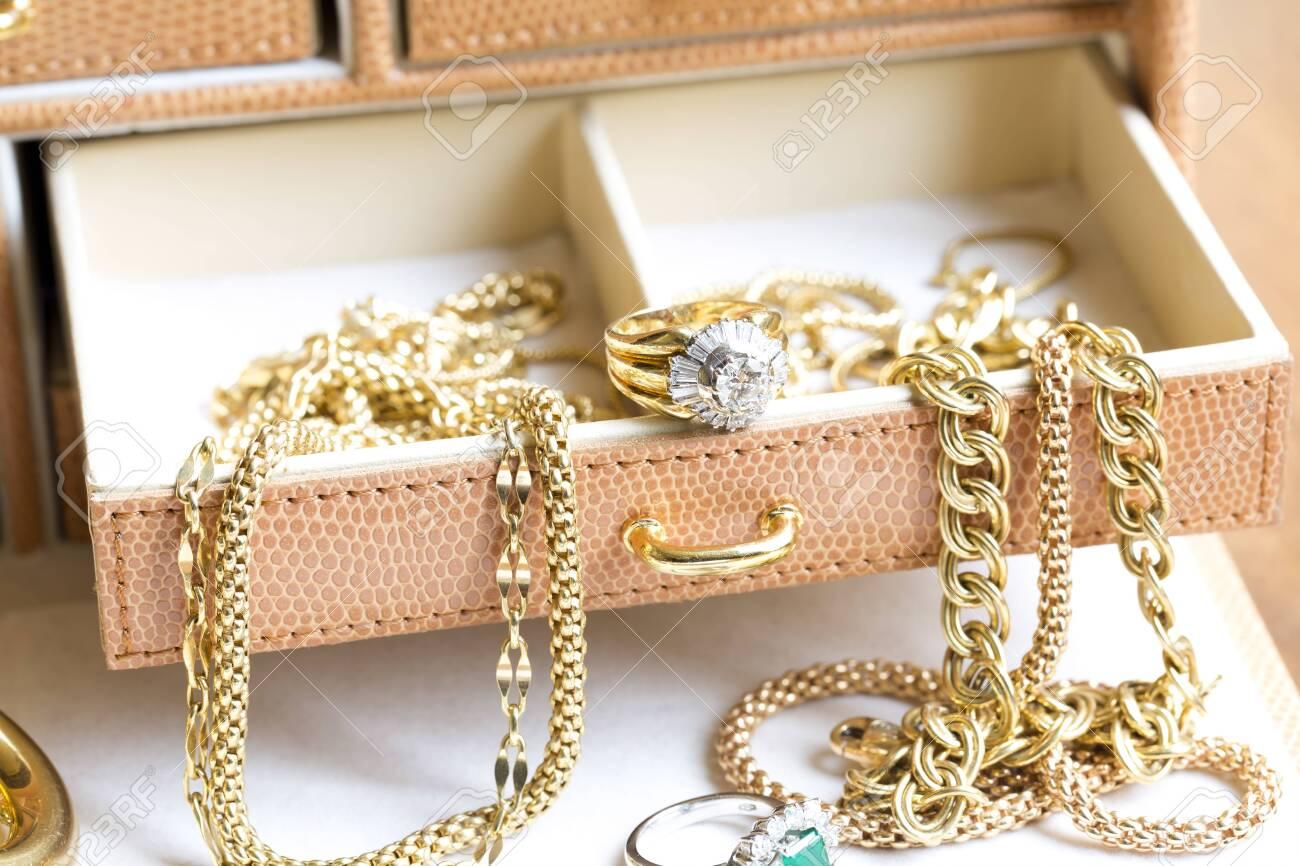 Closeup of gold jewelery with precious stones - 131889637