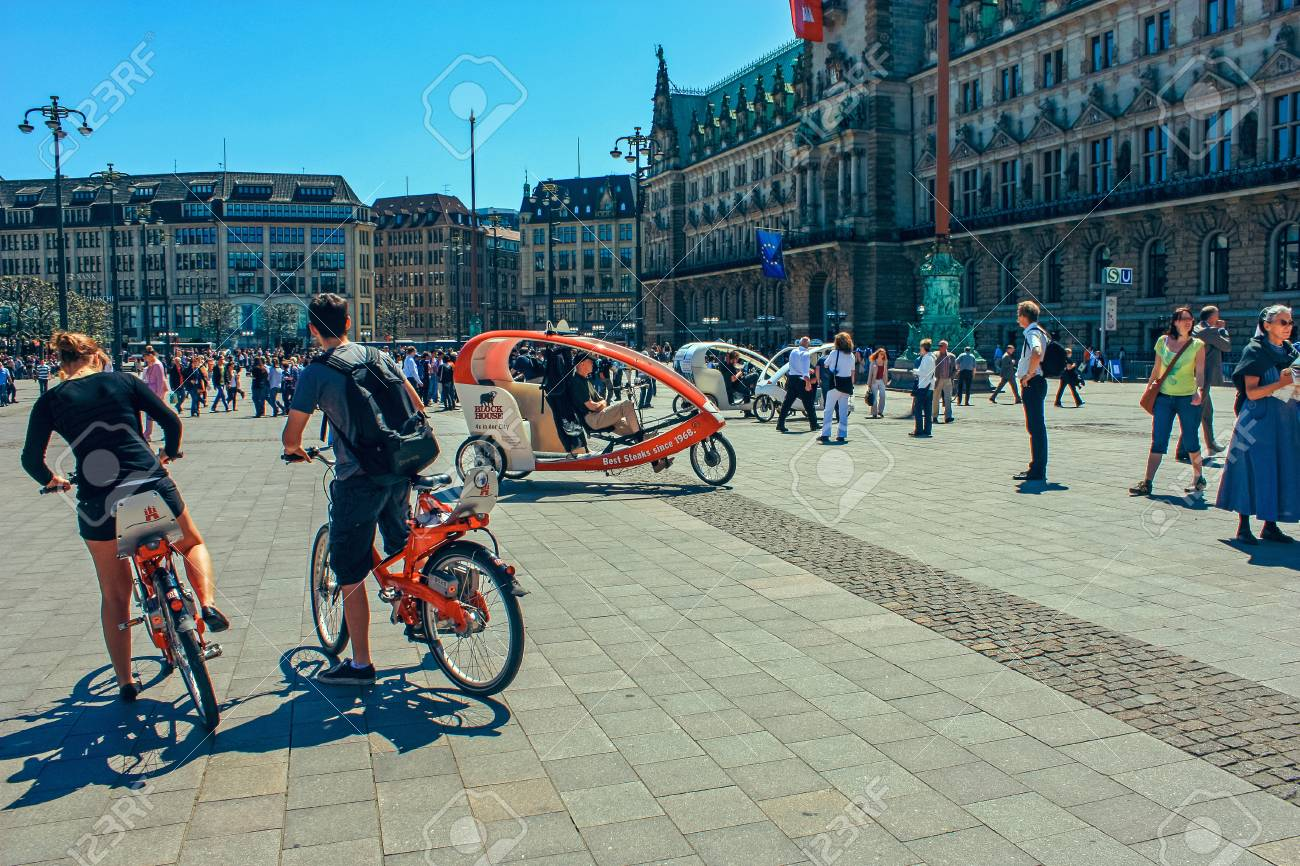 5990d76154440 Cycling taxi for tourists at Market square with Hamburg town hall Rathaus  and blue sky near