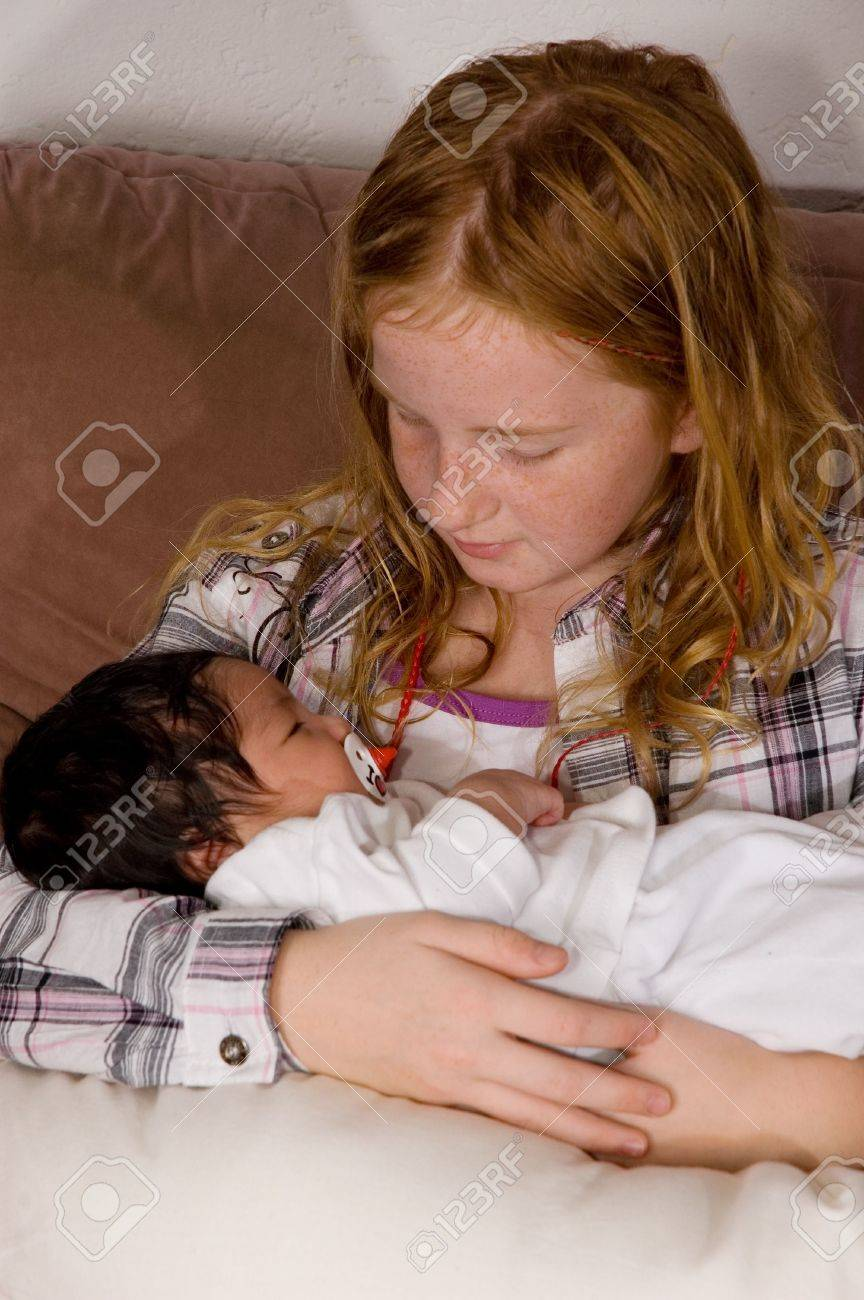 young girl  is holding her 3 weeks old baby niece Stock Photo - 5741411